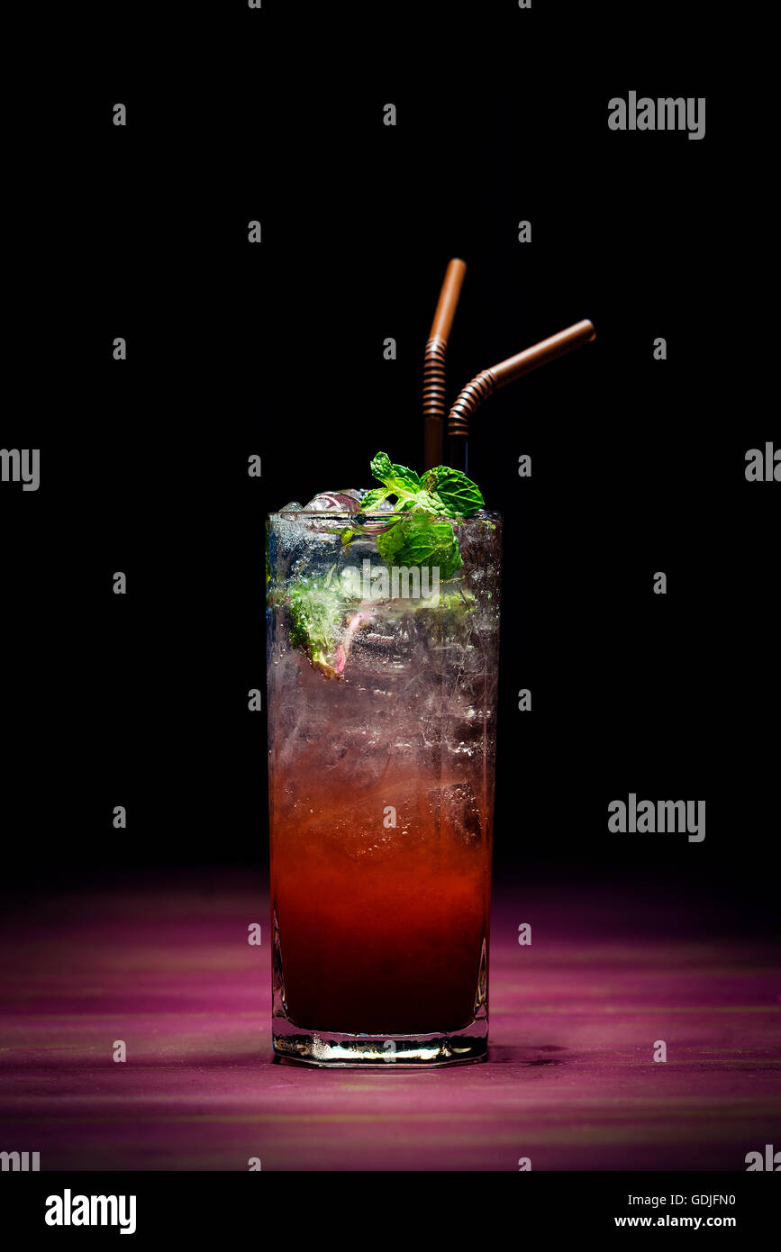 trendy modern strawberry mojito fusion cocktail in sophisticated lounge bar at night - Stock Image
