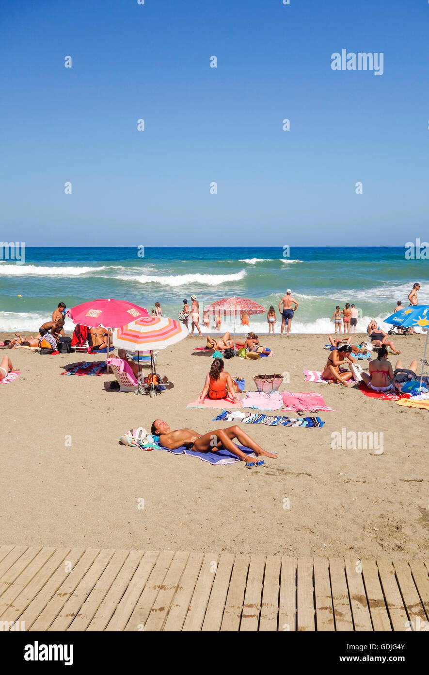 Hot Summer beach with young people sun tanning, Fuengirola ...