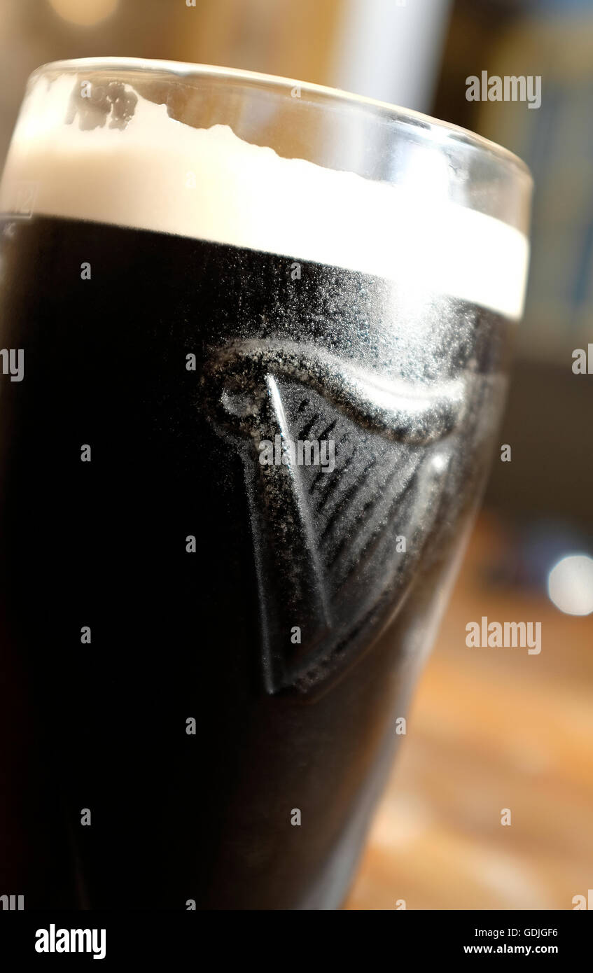 pint of chilled guinness in cool glass - Stock Image