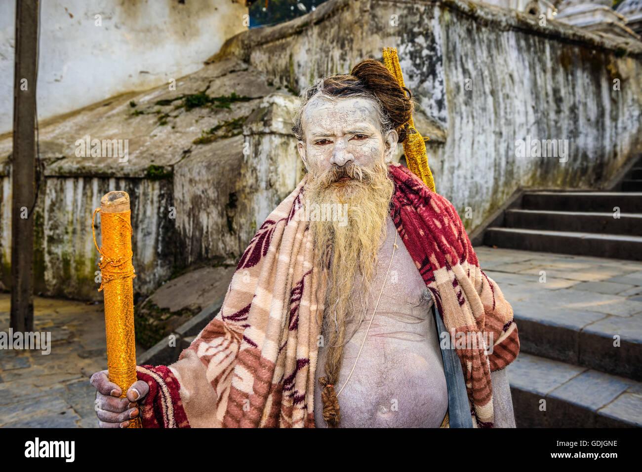 Portrait of wandering  Shaiva sadhu (holy man) with white face painting in ancient Pashupatinath Temple, Kathmandu, - Stock Image