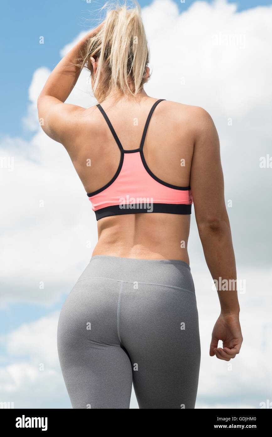 fit woman wearing sports bra and leggings from behind - Stock Image