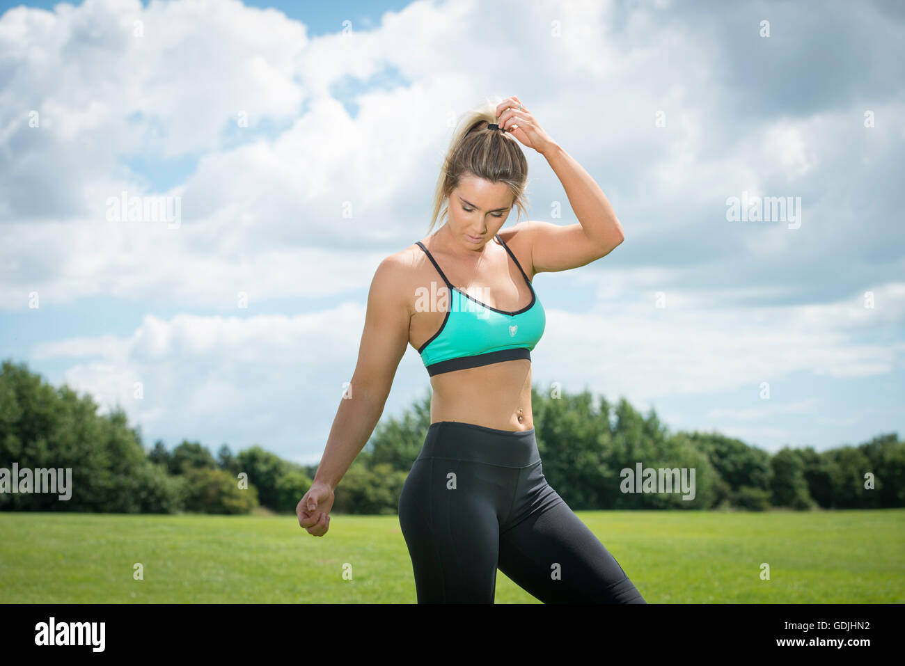 70fc834161 fit woman wearing sports bra and leggings keeping fit - Stock Image