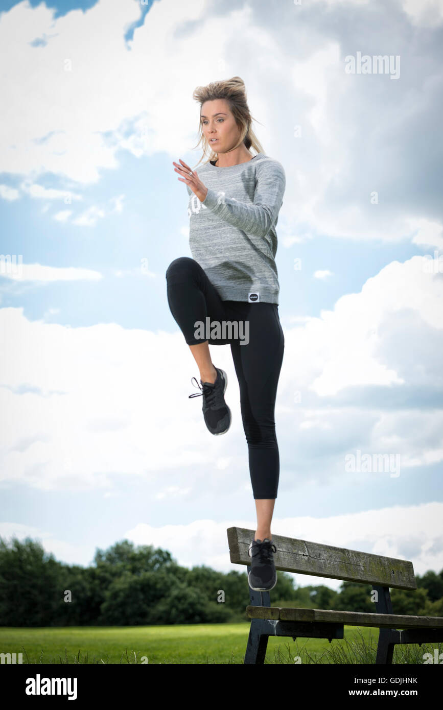 fit woman leaping over a park bench while exercising - Stock Image