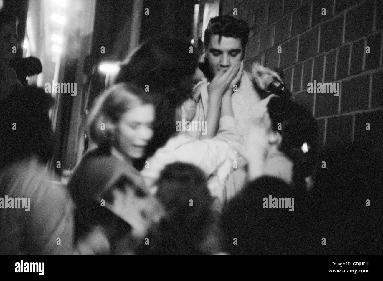 Elvis Presley mobbed by fans after a performance at the University of Dayton Fieldhouse, May 27, 1956. Stock Photo