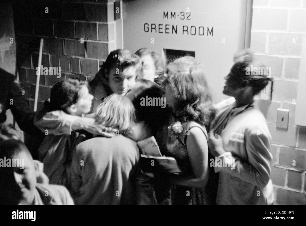 Elvis Presley hugging a group of fans backstage after a performance at the University of Dayton Fieldhouse, May 27, 1956. Stock Photo