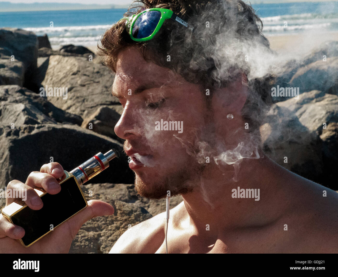 Head and shoulders view of a young shirtless male surrounded by smoke from his e-cigarette he is holding close to - Stock Image