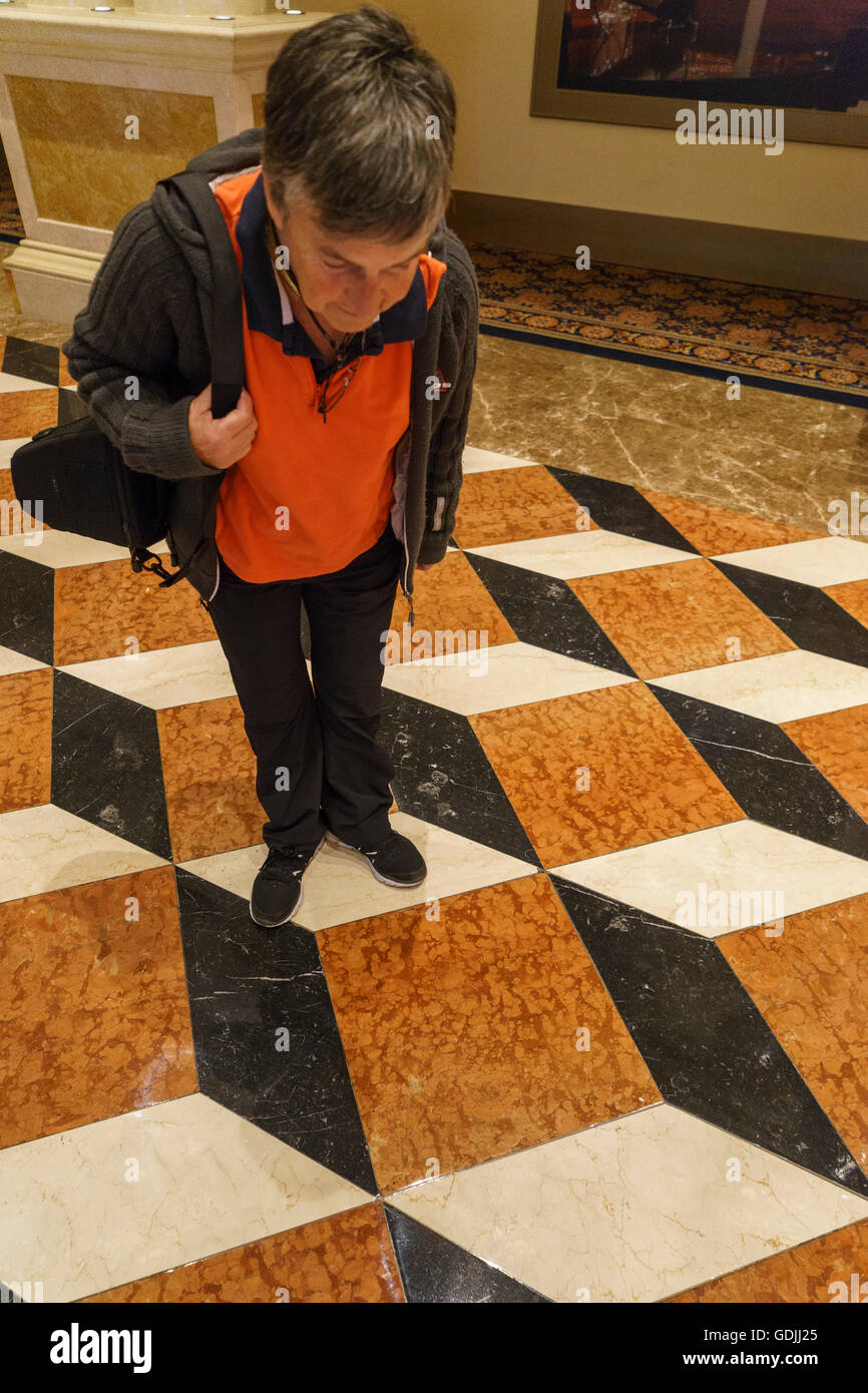 Female looking down at the optical illusion of the flooring in the Venetian Hotel Las Vegas - Stock Image