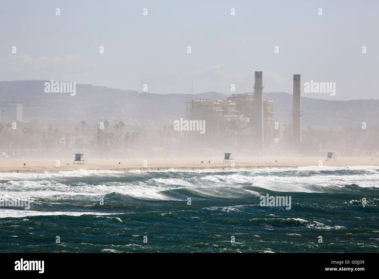 AES Huntington Beach Generating Station seen from Huntington Beach Pier with heavy spray caused by strong winds - Stock Image