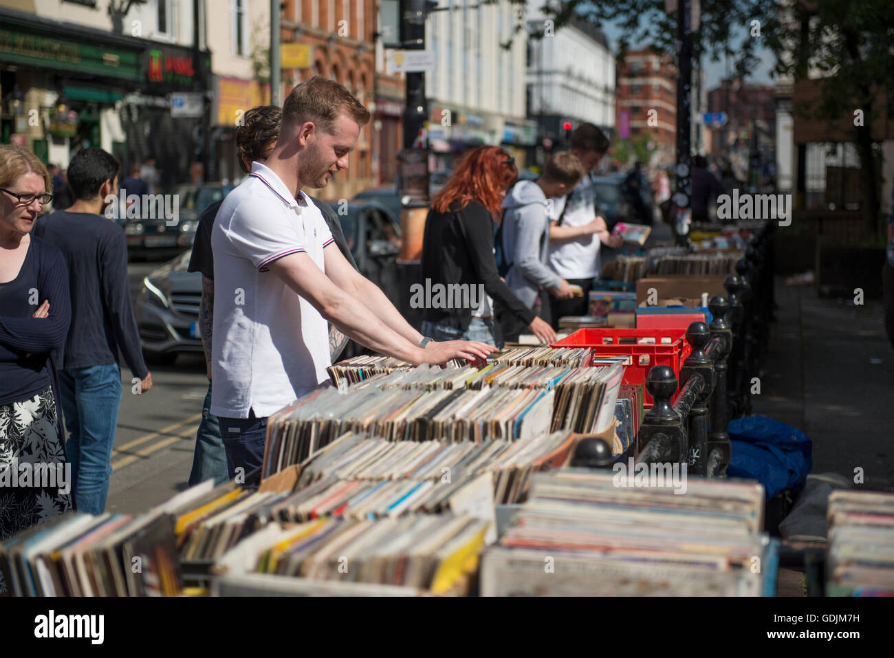 A young man sifts through 2nd hand records for sale at a stall on Thomas Street in the Northern Quarter area of - Stock Image