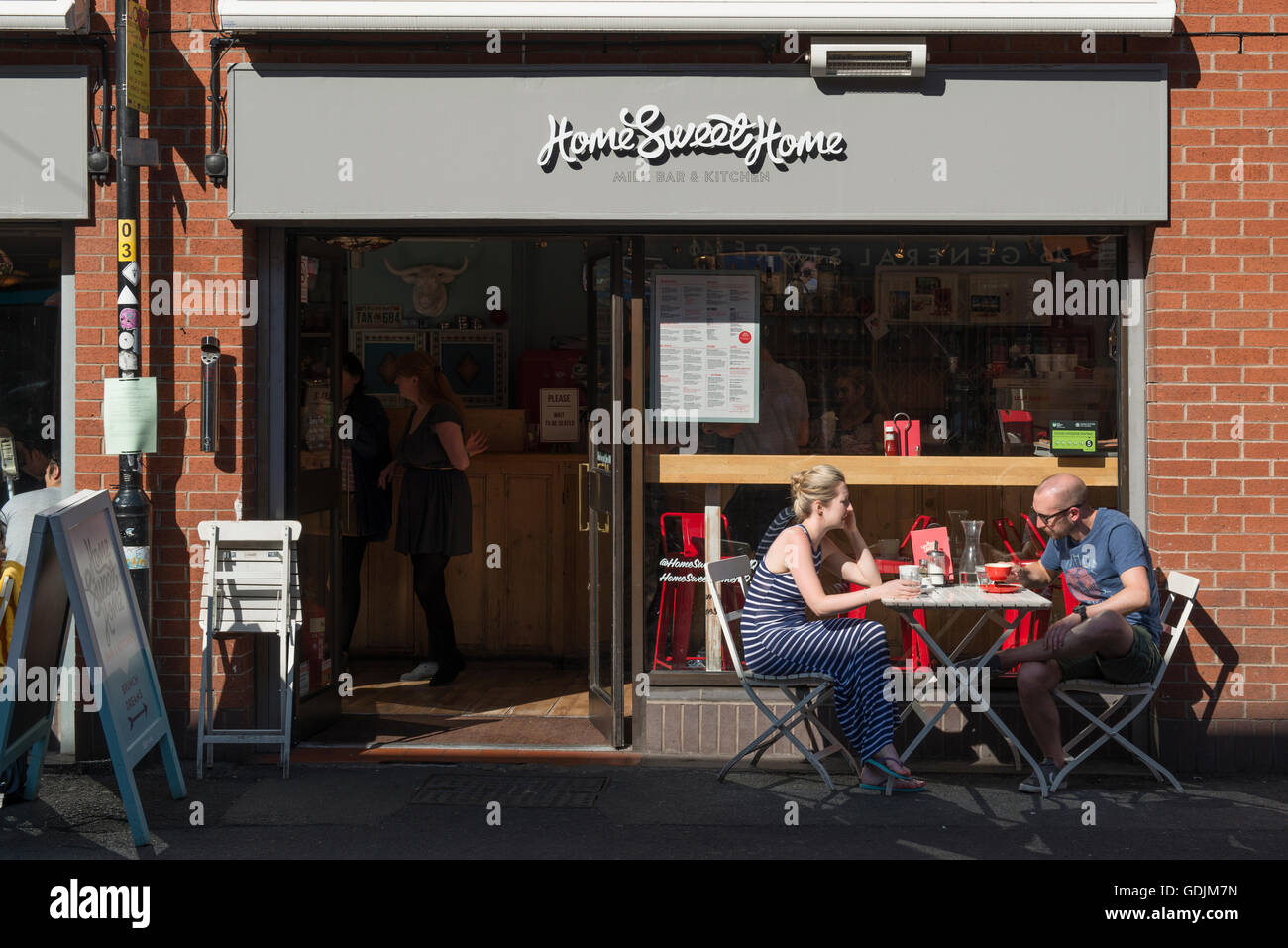 A couple enjoying a drink outside Home Sweet Home located on Edge Street in the Northern Quarter area of Manchester. - Stock Image