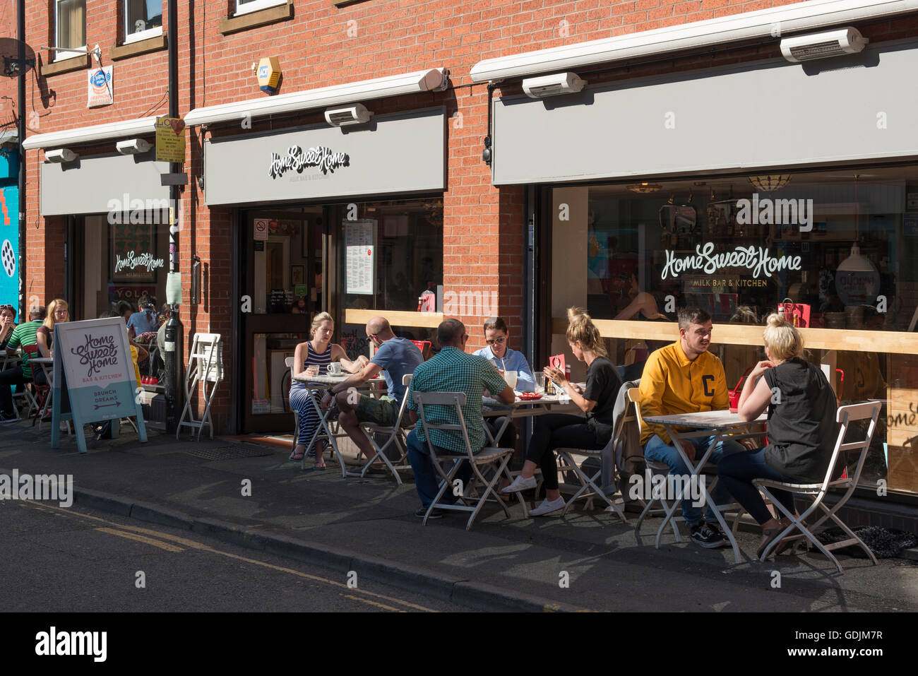 People enjoying a drink outside Home Sweet Home located on Edge Street in the Northern Quarter area of Manchester. - Stock Image
