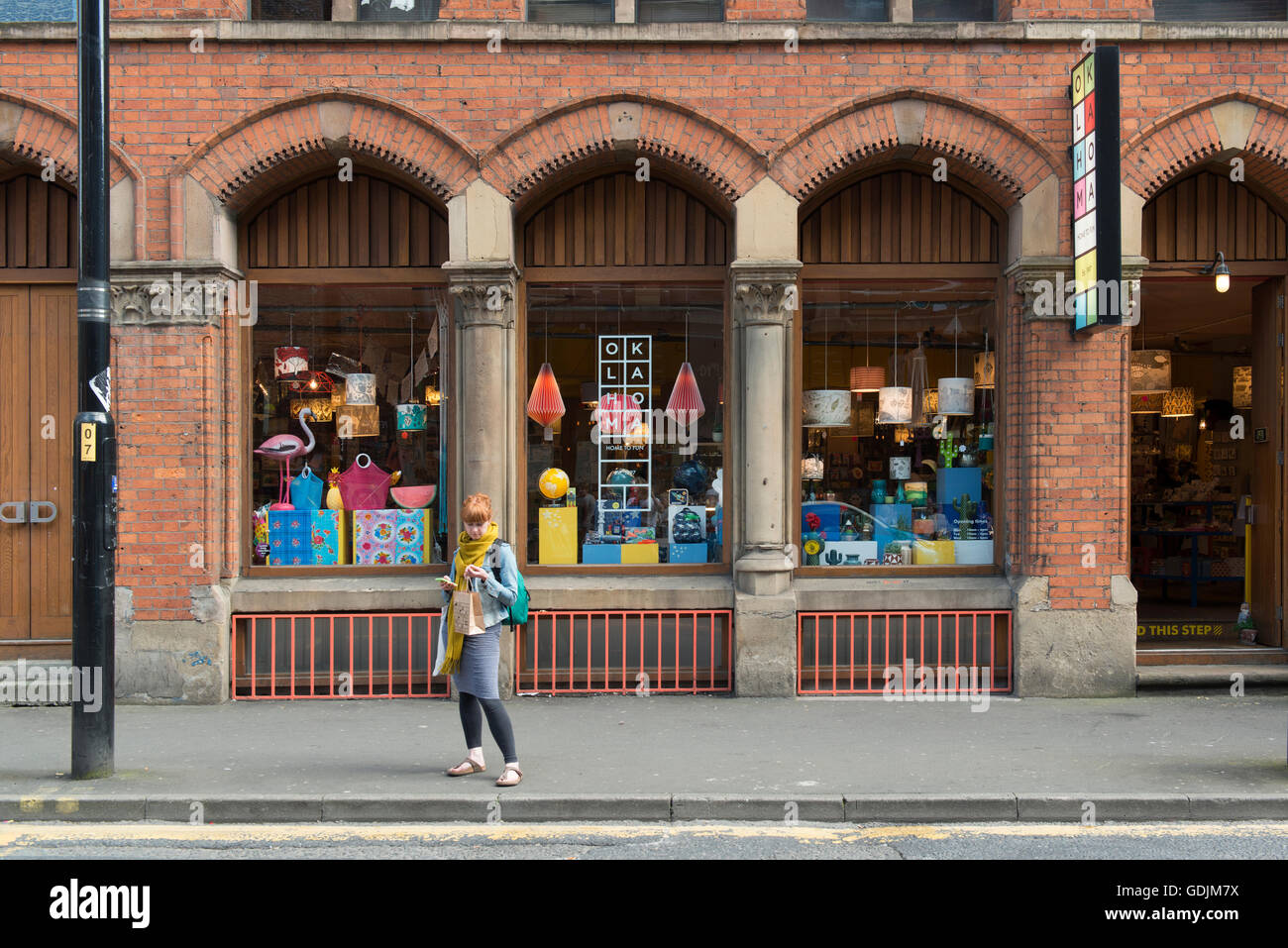A girl waits outside Oklahoma gift shop located on High Street in the Northern Quarter area of Manchester. - Stock Image