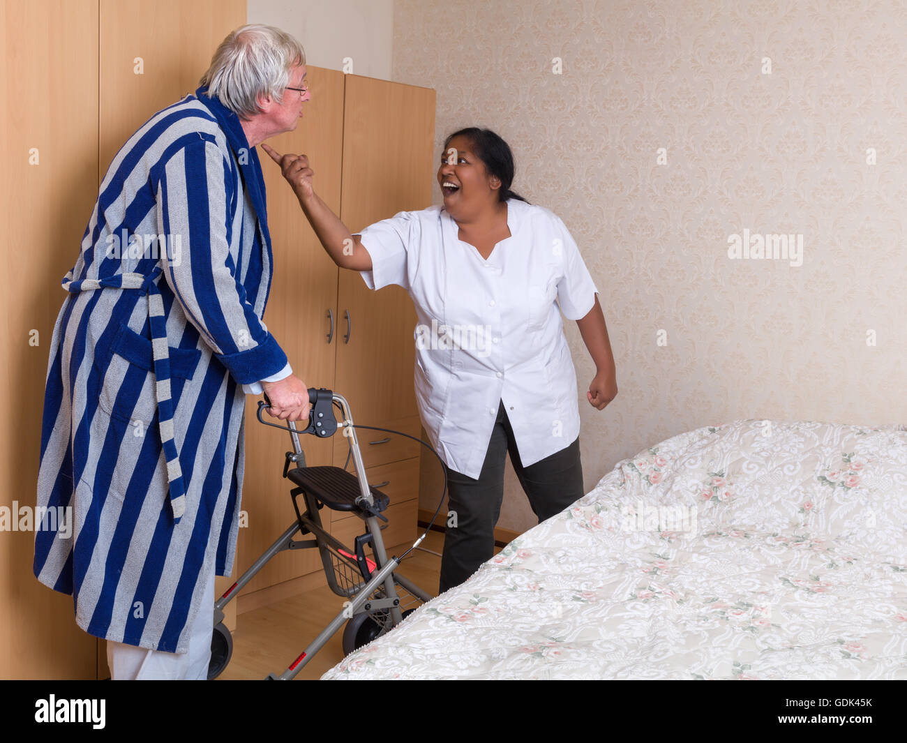 Funny scene of an elderly man having a discussion with his nurse Stock Photo