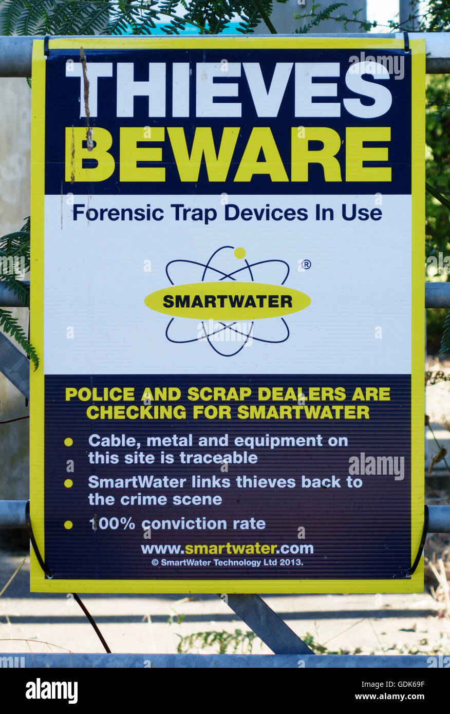 UK. A warning sign on an industrial site stating that SmartWater is in use, a liquid marking system sensitive to - Stock Image
