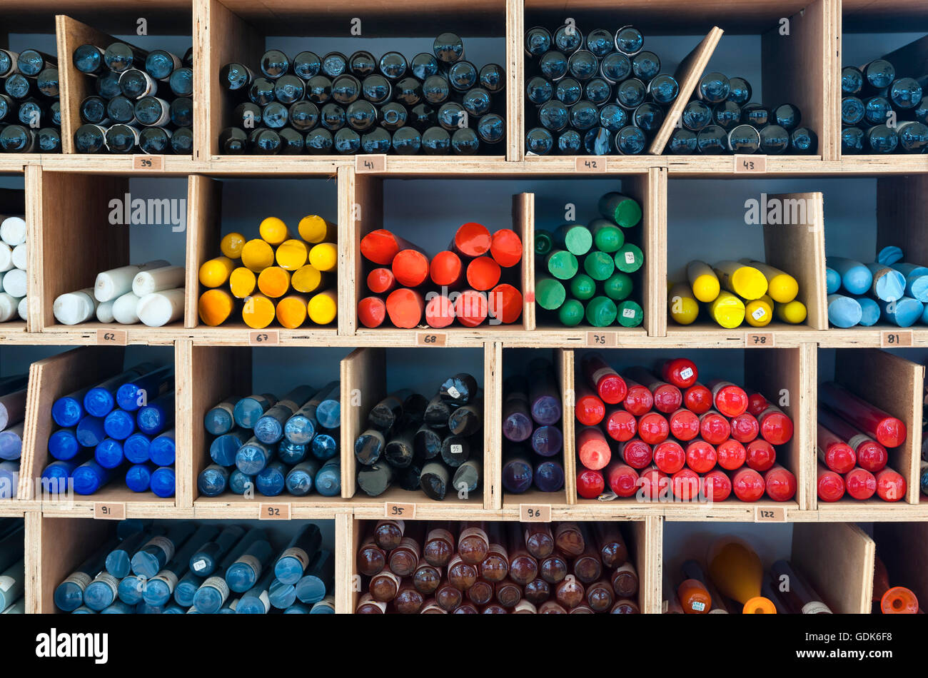 UK. Rods of coloured glass, known as 'cane', awaiting use in a glassblowing studio - Stock Image