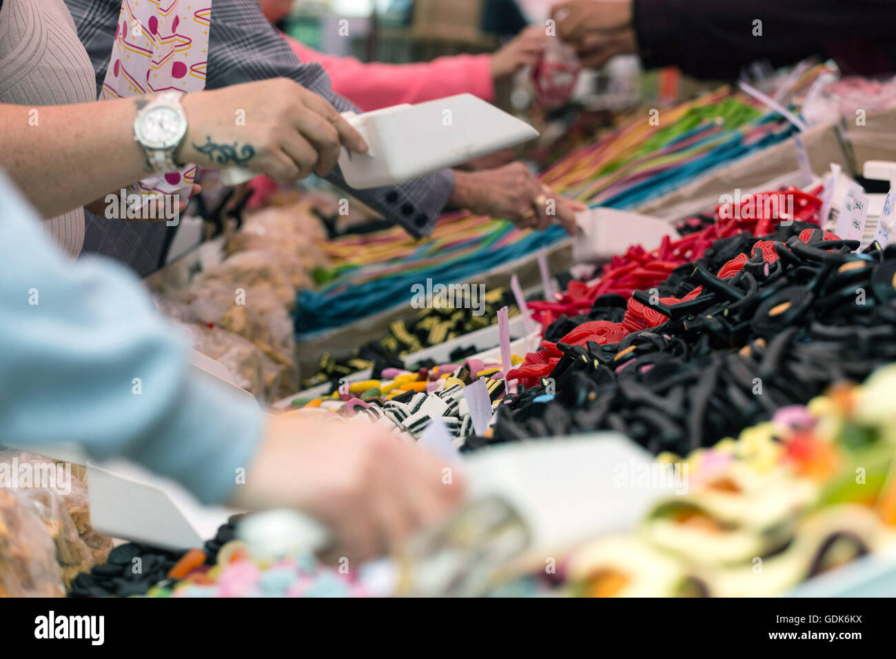 Members of the public help themselves to liquorice sweets, at the Pontefract Liquorice Festival, in Pontefract. Stock Photo