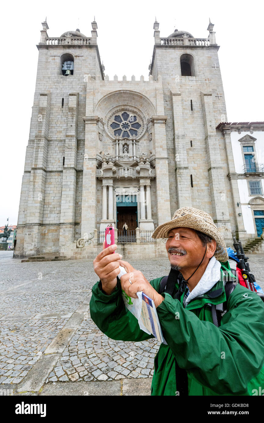Pilgrims from Brazil photographed outside the cathedral with his cell phone, Da Sé Cathedral, Barredo quarter, - Stock Image