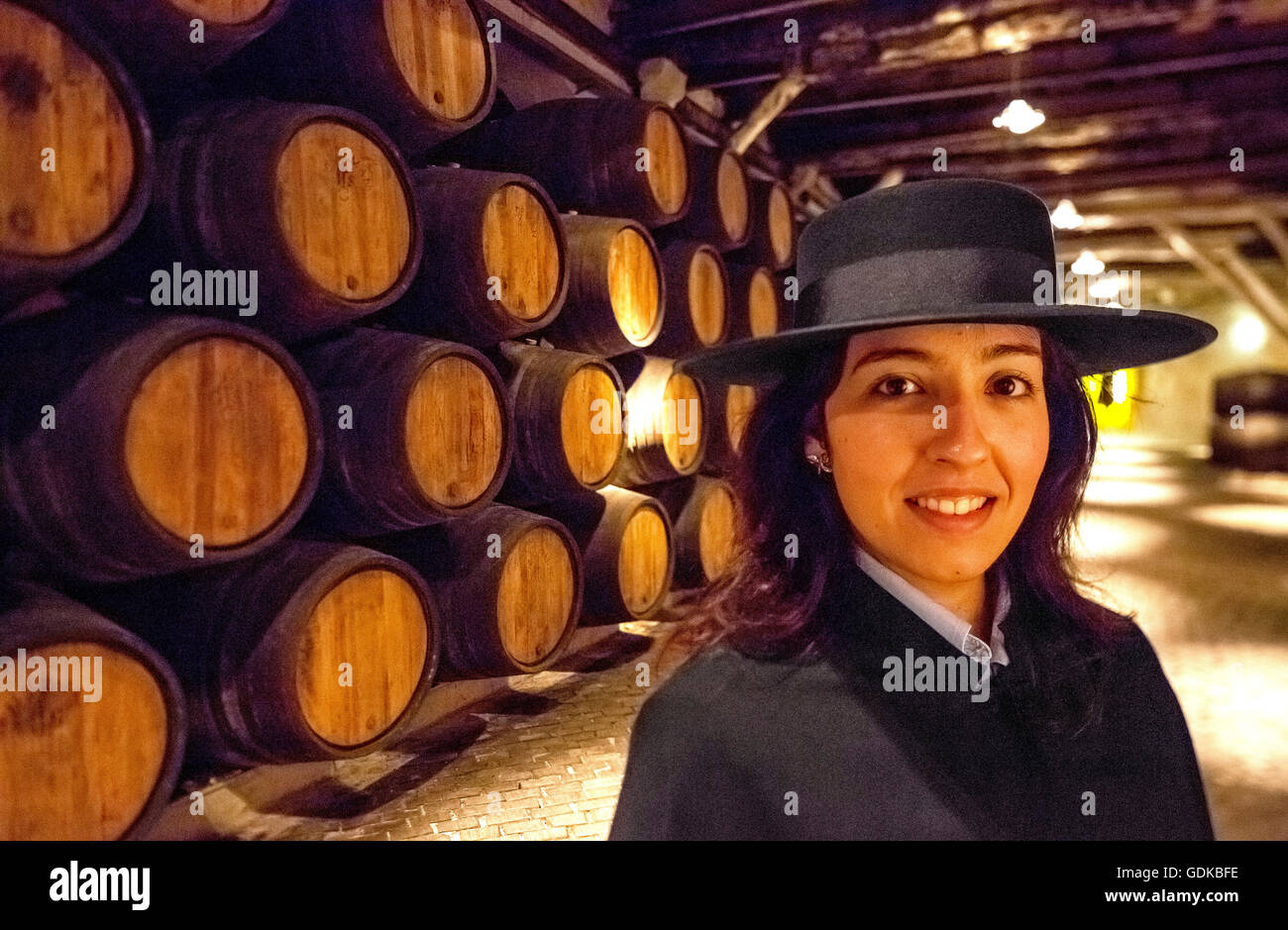 classic tour guide with students robe Zorro hat and cape, Port wine barrels, wine cellar of the winery Sandeman - Stock Image