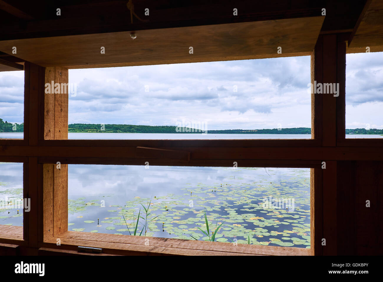 Looking out over lake Sjaelsoe, in Denmark, from within a birdwatch shed - Stock Image
