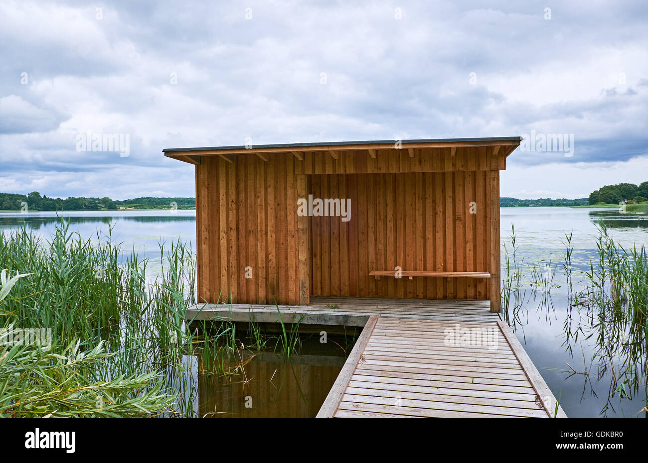 Birdwatch shelter made of wood, at the end of a wooden pier at the border of lake Sjaelsoe in Birkeroed, Denmark - Stock Image
