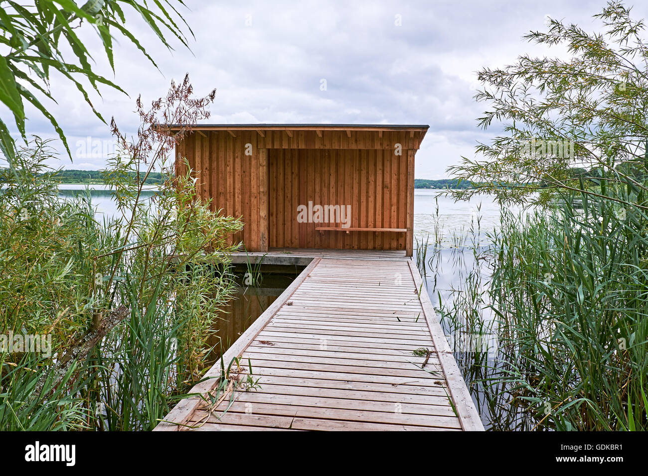 Birdwatch shelter with board on board wood cladding, at the end of a wooden jetty going out in the water of a lake - Stock Image