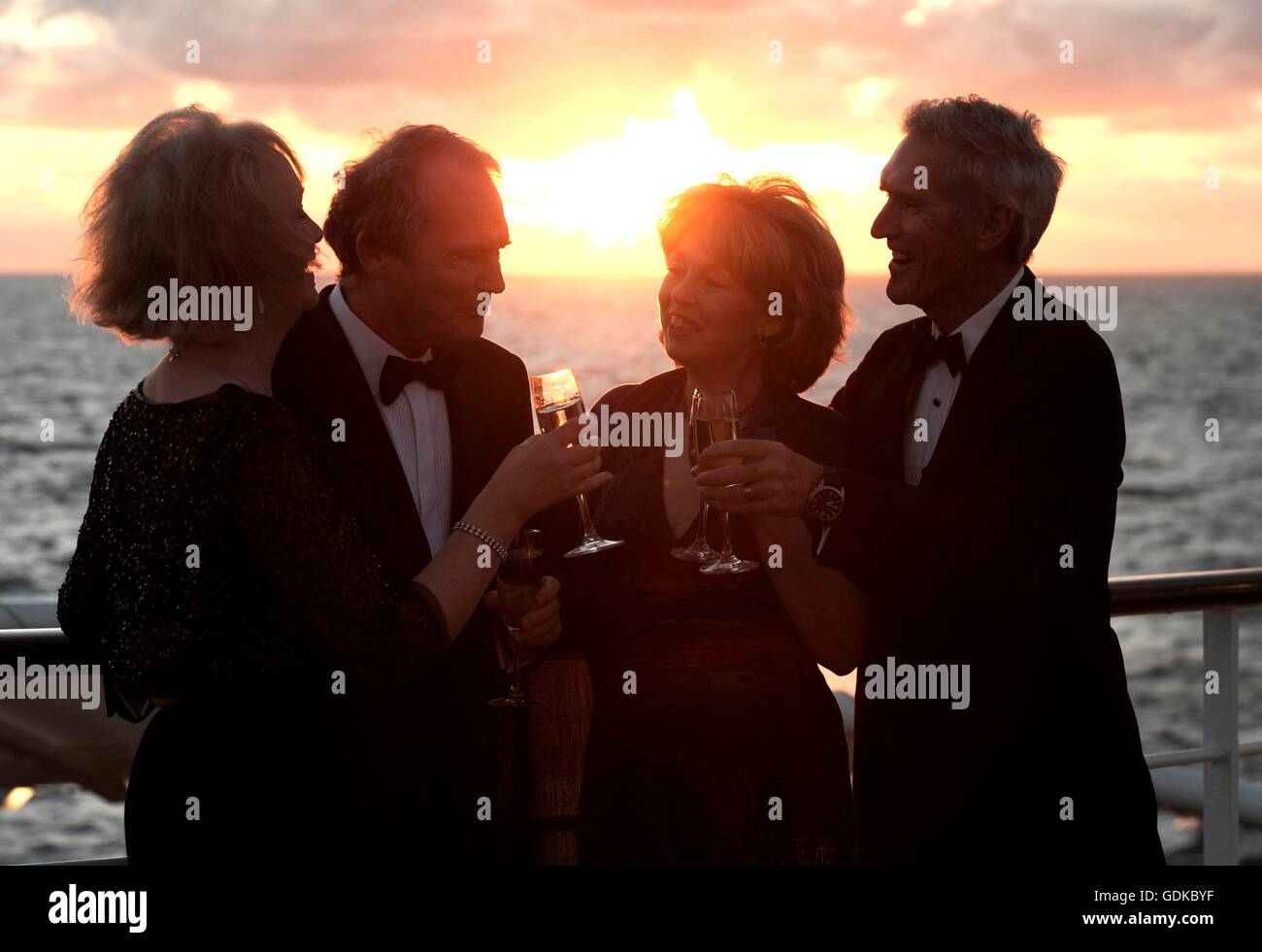 Two couples drinking champaign on a cruise ship deck at sunset - Stock Image