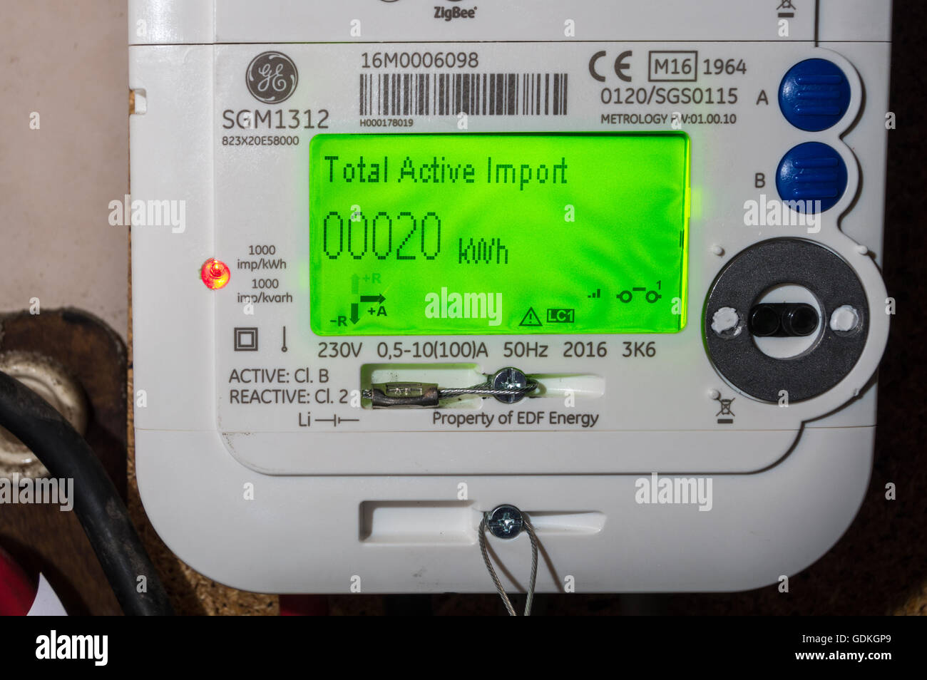 A newly installed EDF GE SGM1312 LCD display smart electricity meter showing reading of 20kWh in a wine cellar in - Stock Image