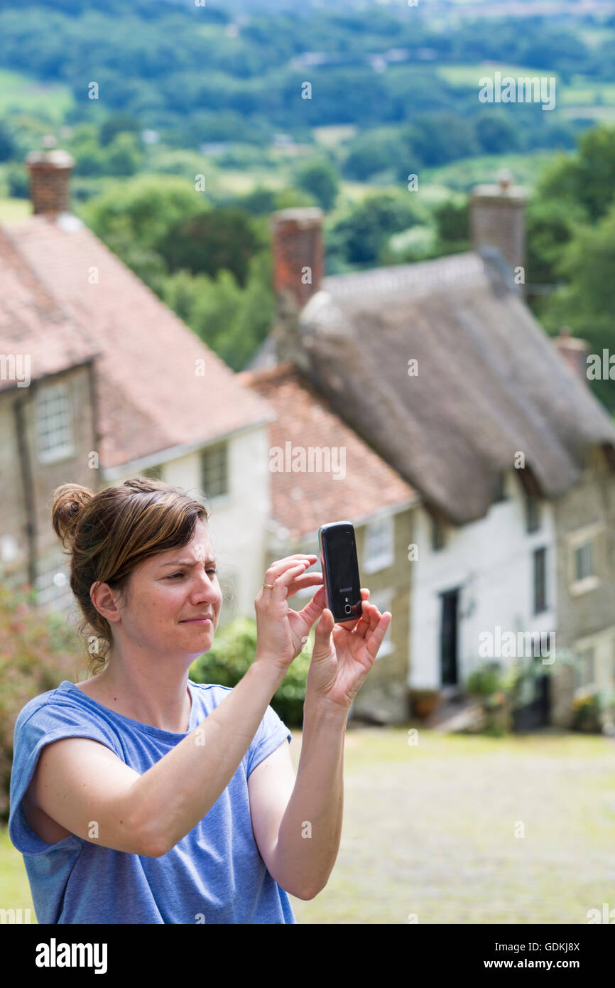 Woman talking a selfie by famous cottages at Gold Hill, Shaftesbury, Dorset in July Stock Photo