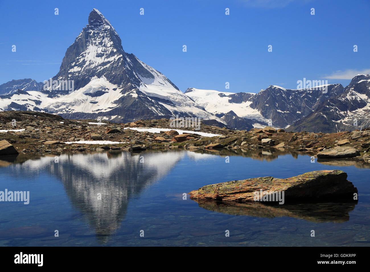 Matterhorn reflected into alpine lake, Switzerland - Stock Image