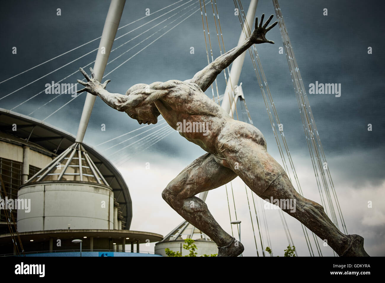 A statue of a sprinter the moment after the starting pistol near to the City of Manchester Etihad Stadium - Stock Image