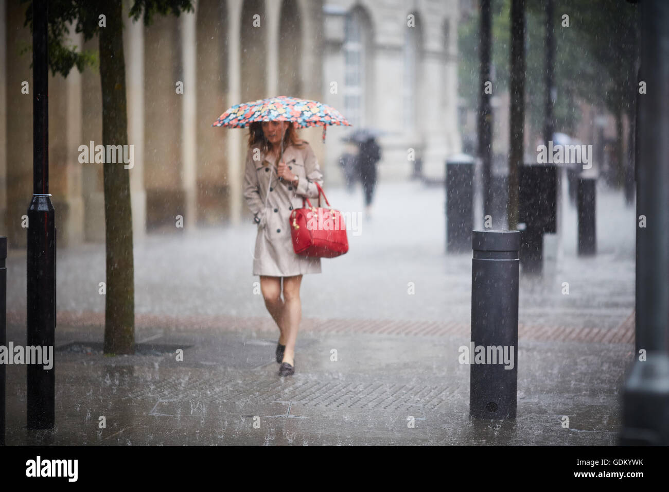 Heavy rain in Manchester city centre    Rain raining down pour  wet soaked soaking through  umbrella bouncing of - Stock Image