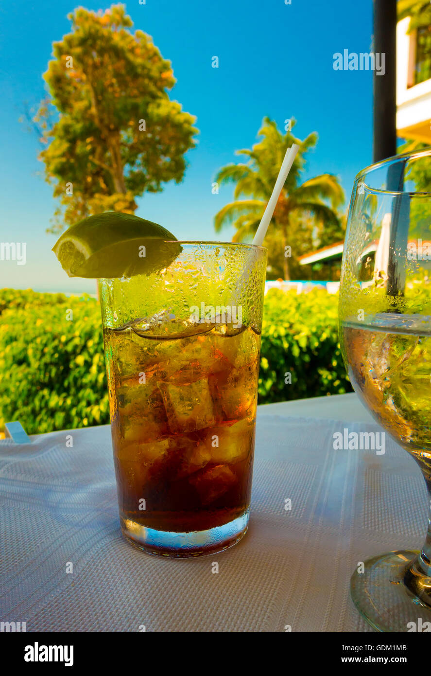A Cuba Libre (Rum and coke) sitting on a table overlooking a resort. Costa Rica, Central America. - Stock Image