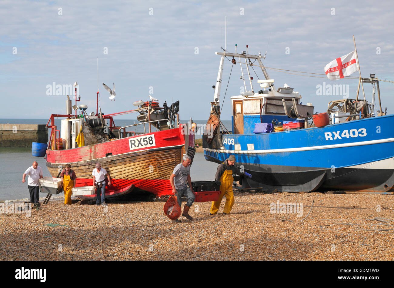 Hastings fishermen unloading fish on the Stade beach, East Sussex, England, UK - Stock Image