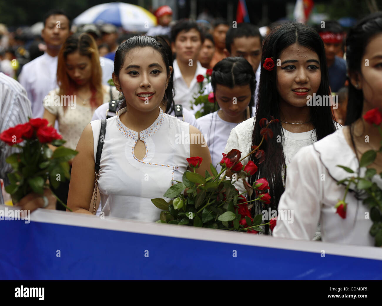 (160719) -- YANGON, July 19, 2016 (Xinhua) -- People hold flowers as they wait outside the Martyrs' Mausoleum - Stock Image
