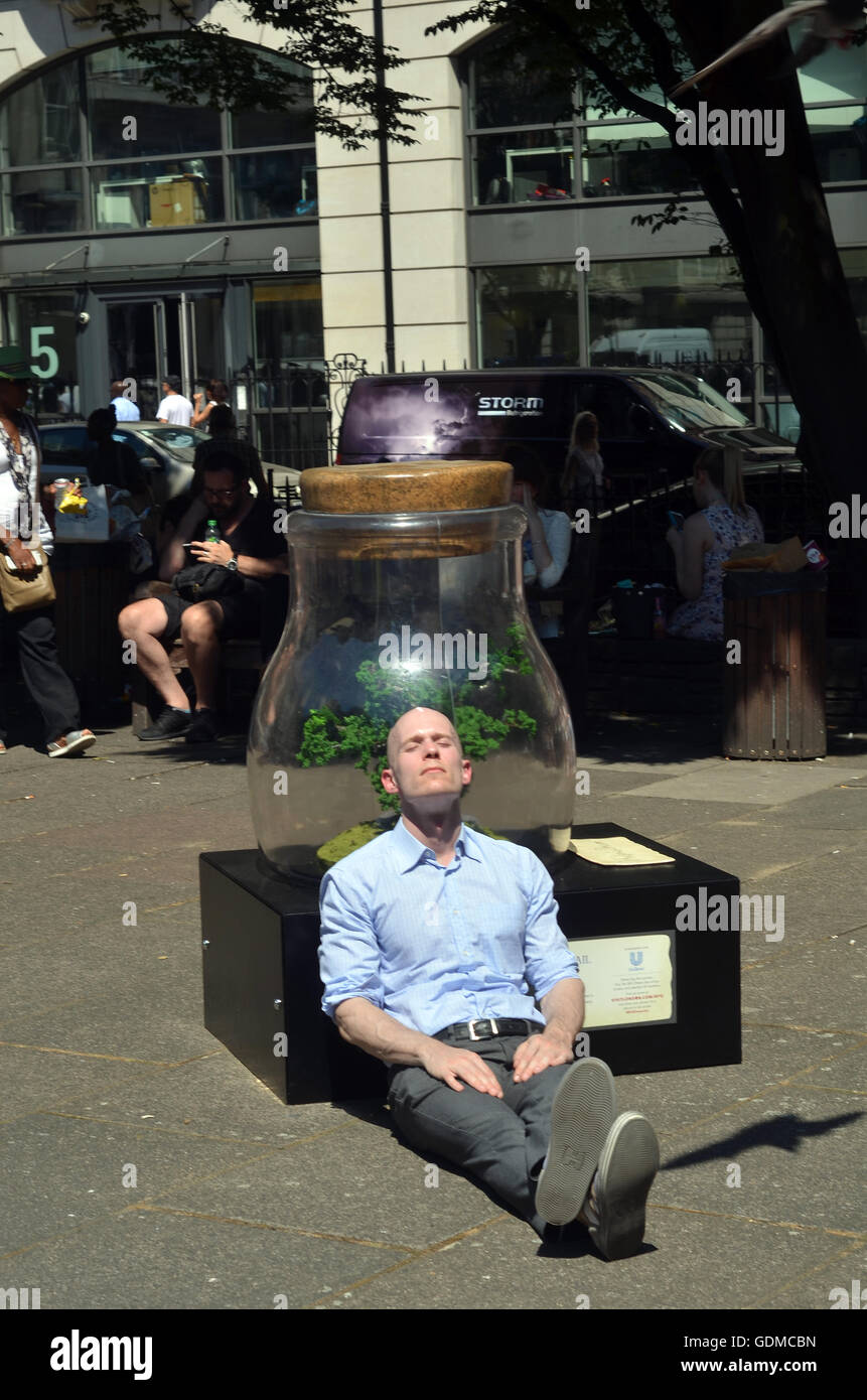 Golden  Square London UK 19 July 2016  A man snoozes against a sculture in Golden Square. Lunchtime crowd relax - Stock Image