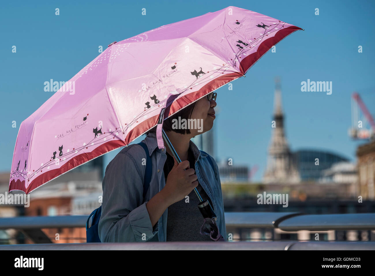 London, UK. 19th July, 2016. Tourists (one with a pink parasol for UV protection) cross the Millennium Bridge under - Stock Image