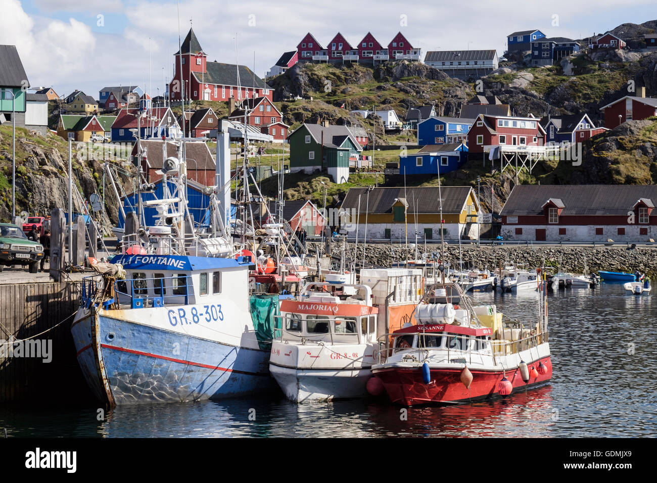 Greenlandic fishing boats moored in northernmost year-round ice-free arctic port with old town behind in summer. - Stock Image