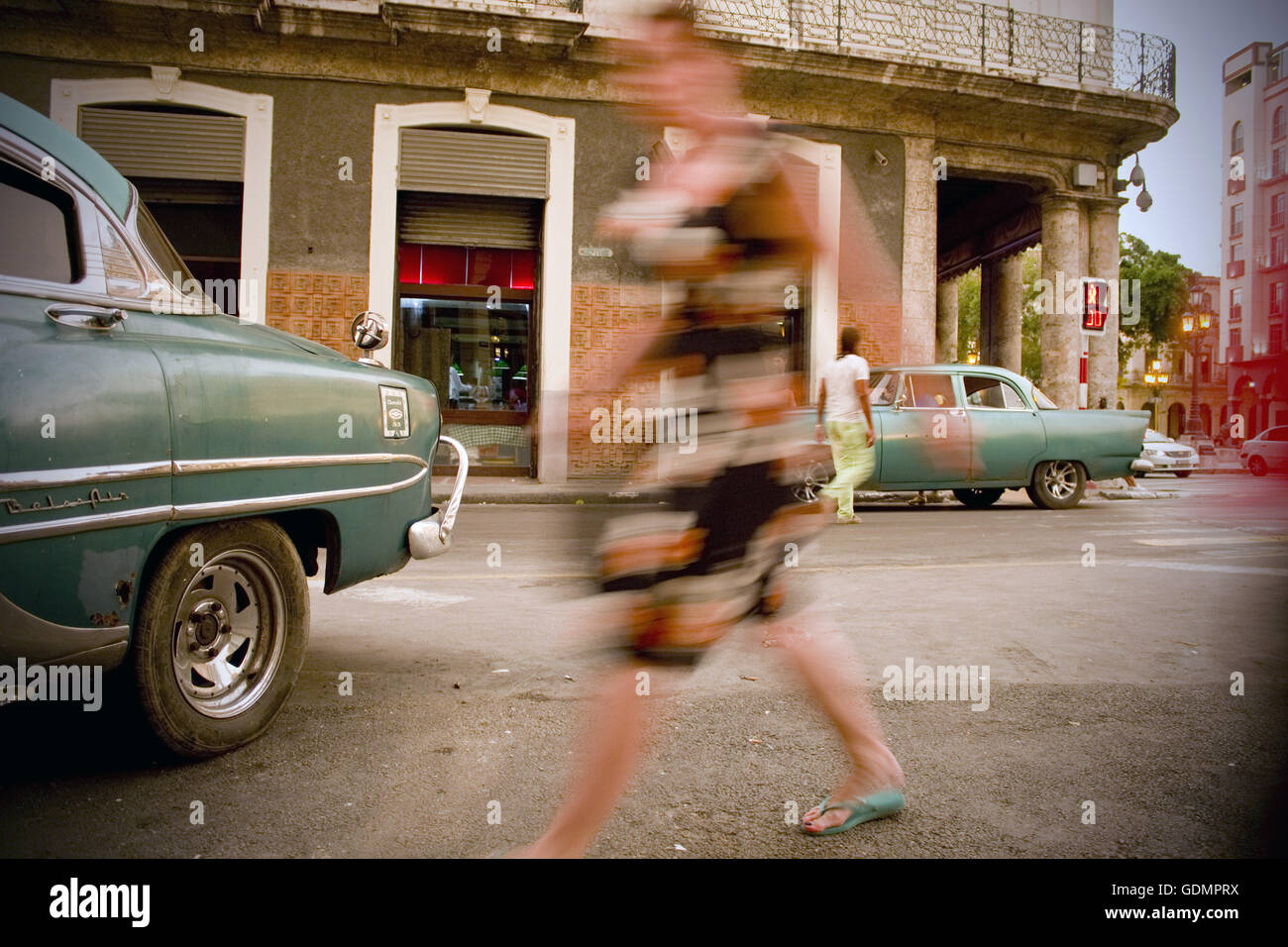 Slow motion blur of woman walking amongst classic old cars in downtown Havana, Cuba - Stock Image