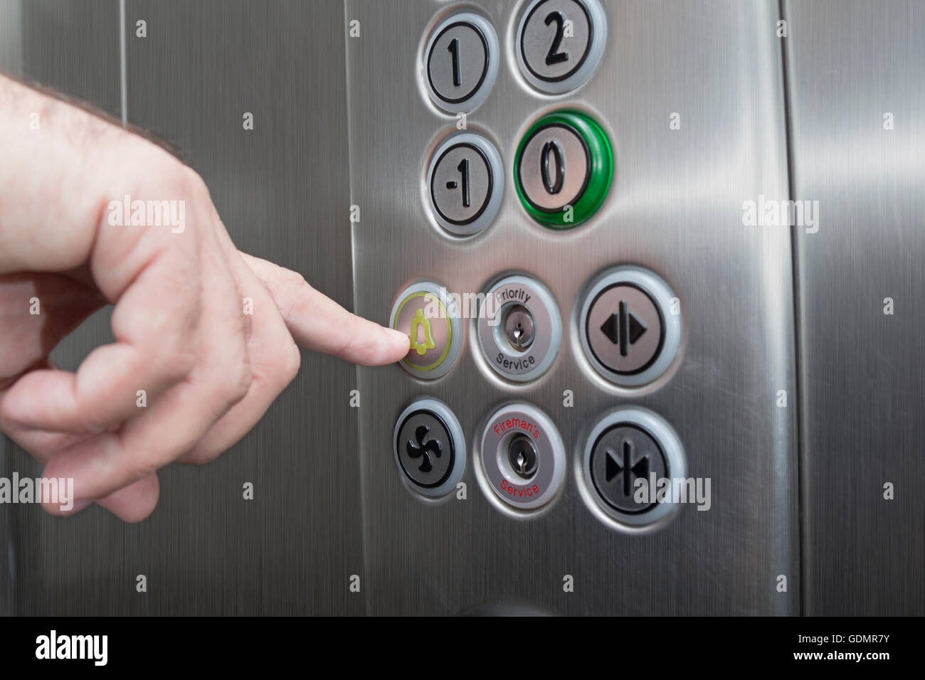 Forefinger pressing the alarm button in the elevator - Stock Image