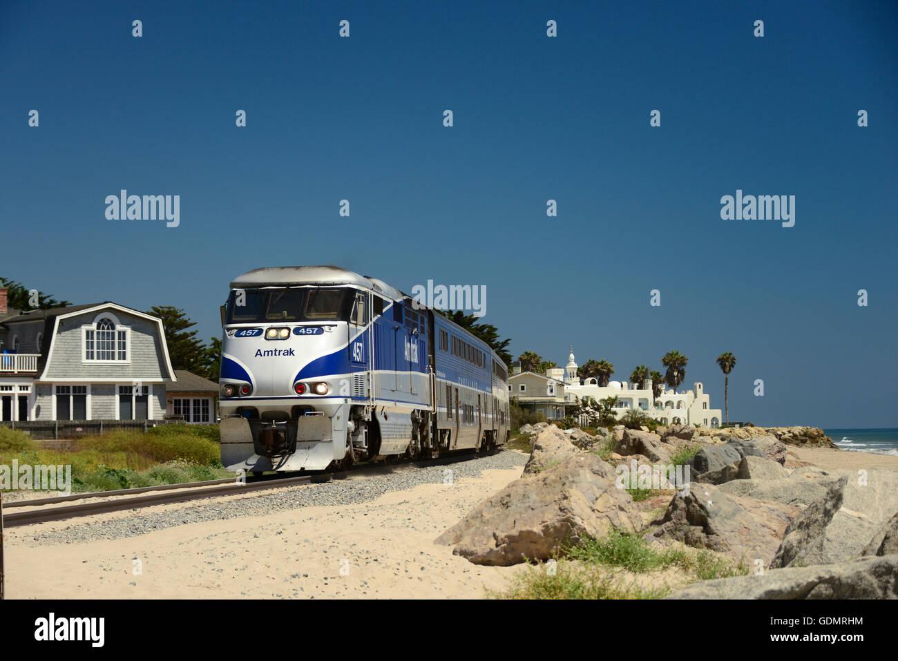 Amtrak Surfrider passenger train on tracks alongside Pacific Ocean beach near Santa Barbara on Central Coast of - Stock Image