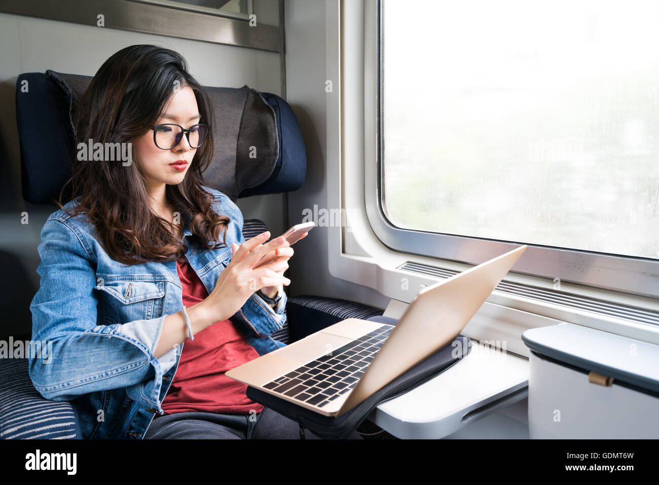 Cute Asian woman using smartphone and laptop on train, copy space on window, business travel or technology concept - Stock Image