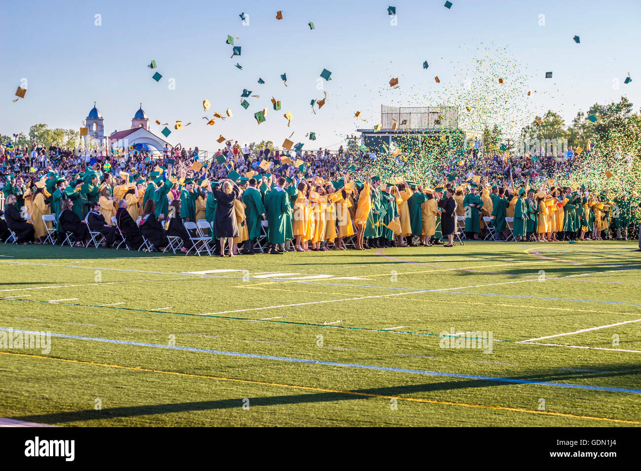 Ground level view of the culmination of a high school graduation taking place on a football field while students - Stock Image