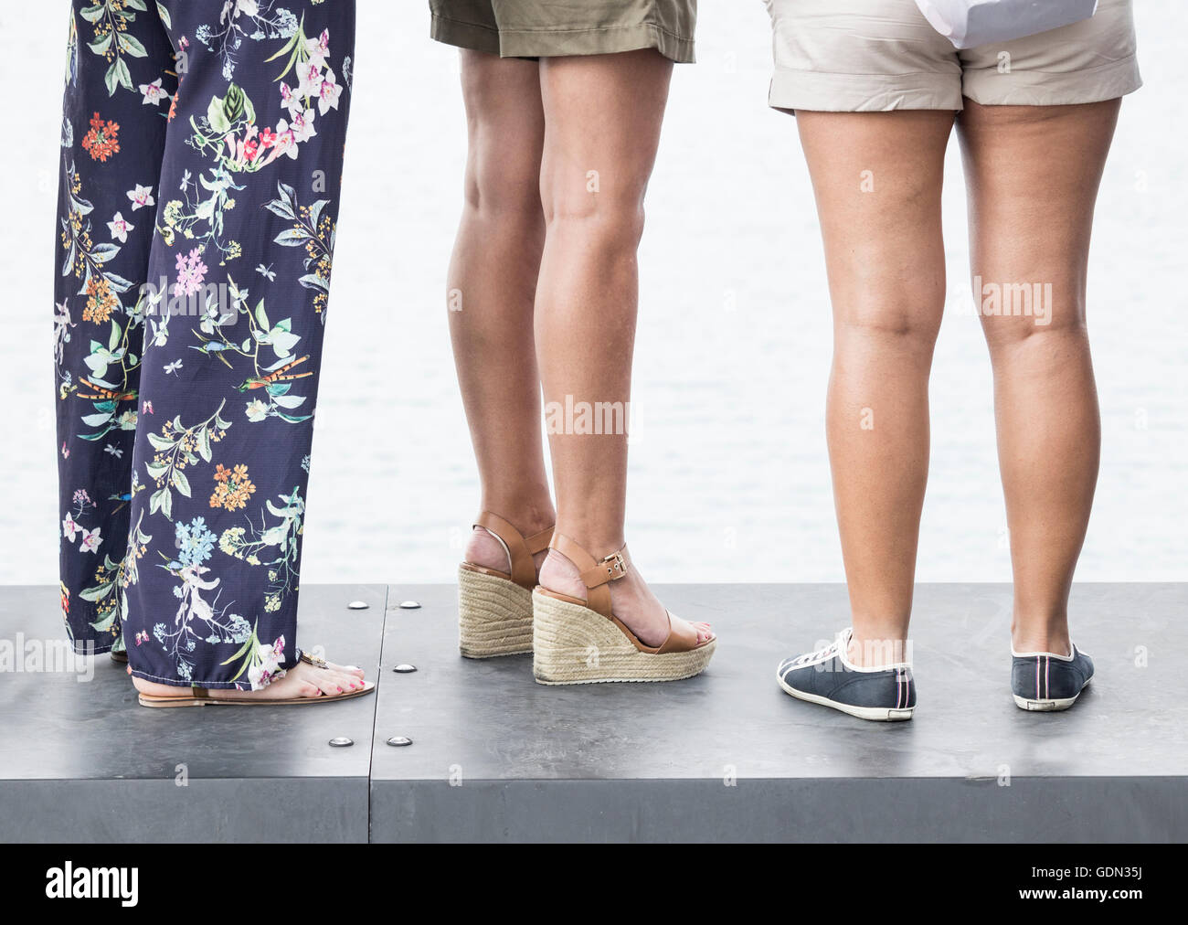 Three women wearing different types of footwear: heels and flats - Stock Image