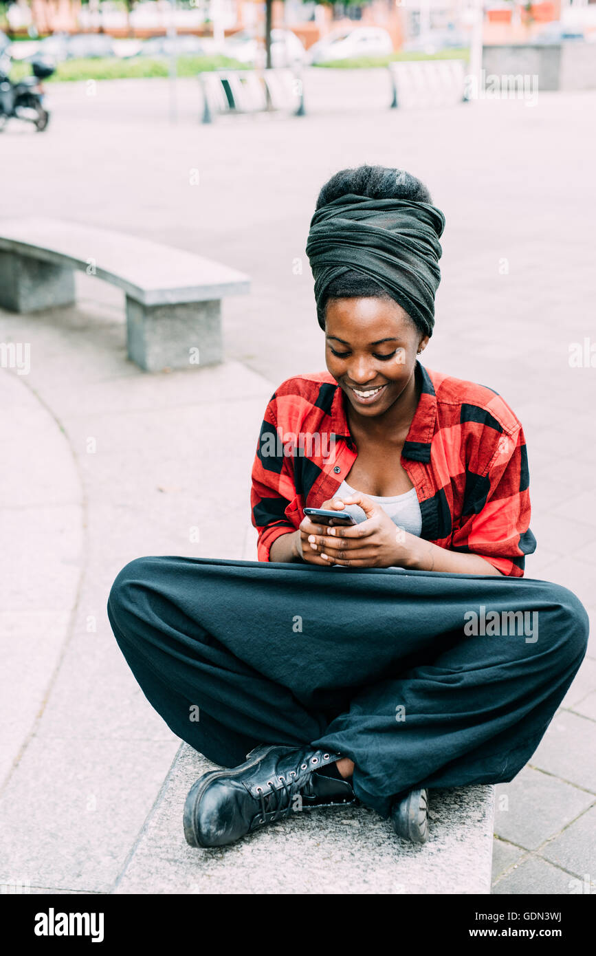 Young beautiful black woman sitting leg crossed on a bench, tapping and looking at the screen of a smart phone hand - Stock Image