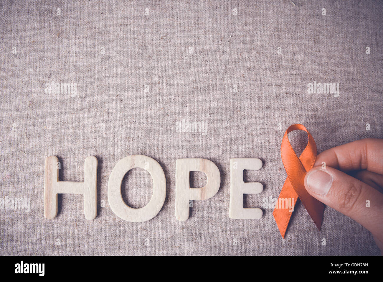 Orange Ribbon with HOPE wooden letters, toning, - Stock Image