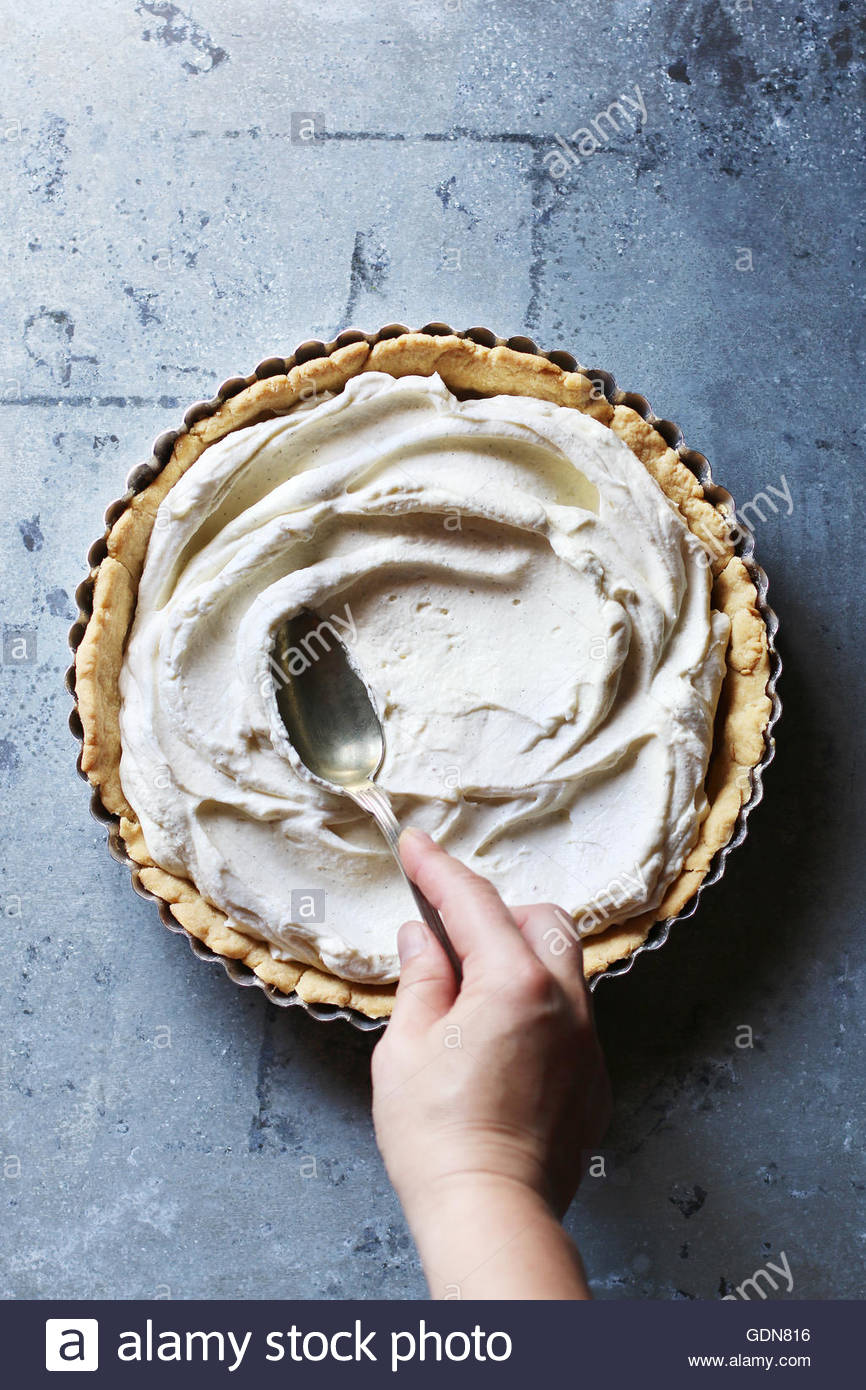 Hand spreading with the back of a spoon the whipped cream filling over the bottom of a tart - Stock Image