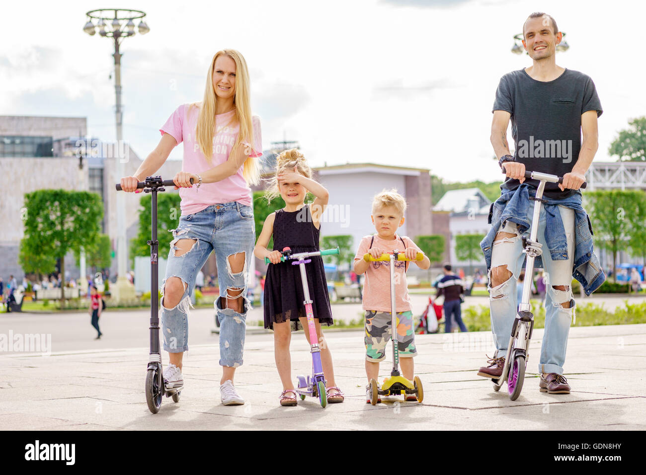 Young modern family with scateboard scooter. - Stock Image