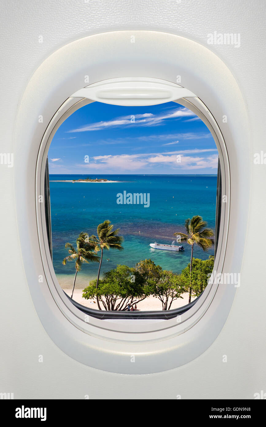 Window of an airplane from inside, view on a tropical beach and sea Stock Photo