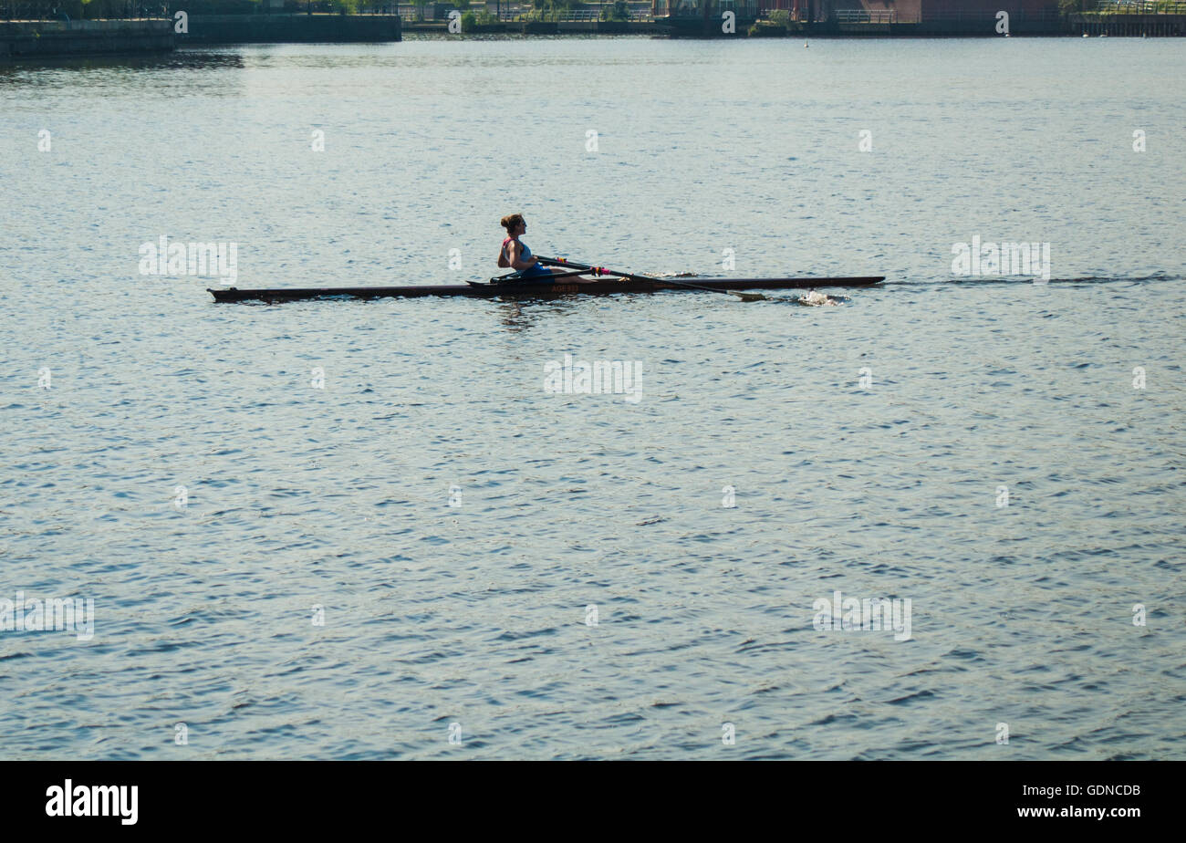 Salford Quays - female rower on the Manchester Ship Canal - Stock Image