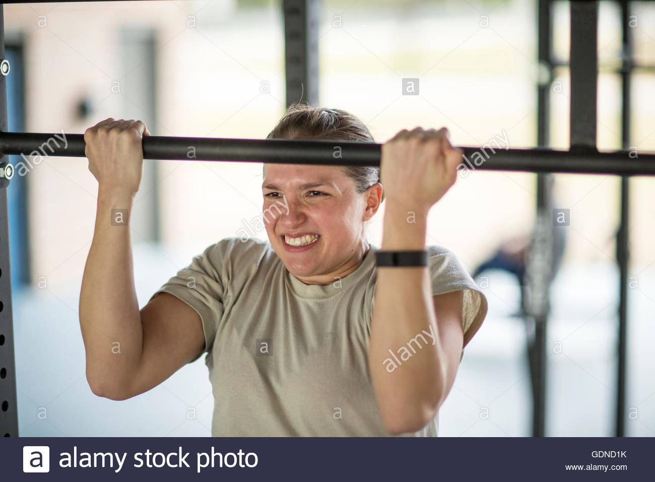 Determined female soldier doing pull ups at military air force base - Stock Image